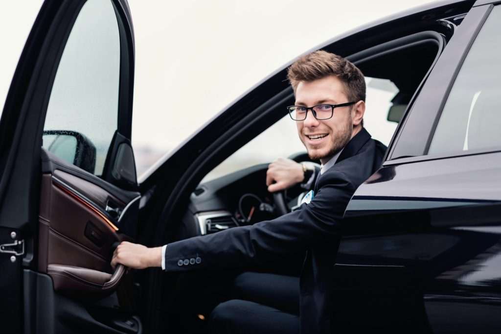 Young businessman driving alone in his luxury car